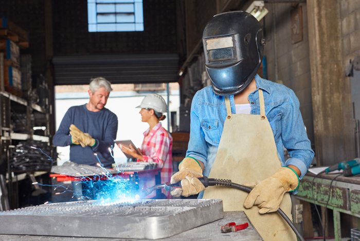 3 people in photo with one of them welding