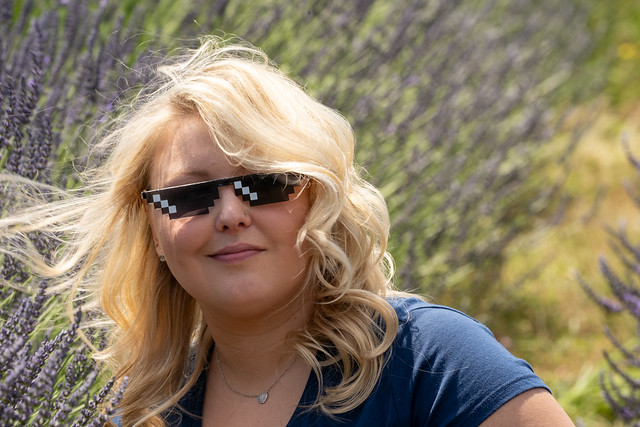 Blonde adult woman wearing thug life sunglasses sits in a field of lavender, looking smug