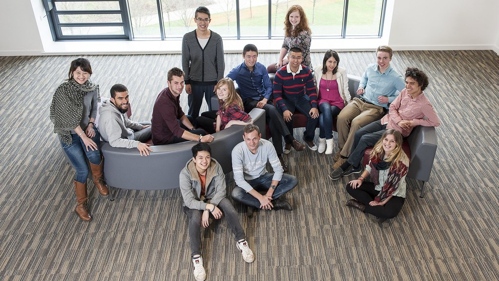 A group of students sitting together looking and smiling at the camera.