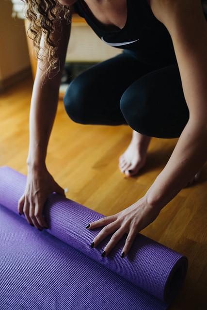 Yogi unrolling yoga mat on the floor.