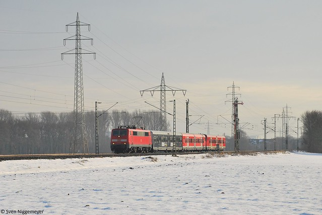 Aus dem Gegenlicht fuhr 111 128 mit einer Fahrzeugüberführung, bestehend aus einem x-Wagen und 2 bxf-Wagen, durch Neuss am Abzweig Weissenberg am 5.01.11