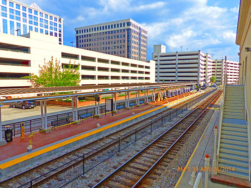 churchstreetstation restoredchurchstreetstationbuilding skyscraperstothenorth skyscraperstotheeast skyscraperstothesouth partlycloudy bluesky scatteredclouds highvantagepoint highpointofview pov stairs lookingdown sunrail orlando orlandometroarea orlandometropolitanarea downtownorlando downtown orlandoflorida florida fl orangecounty unitedstates usa us america commuterline trainstation traindepot beforeofficialopening employeepractice testingthcommuterline testingthecommutertrain sunrailtesting passengertrains railcars rightofway row commercialcenter orangecountyfl originalstationturret circularturret marooncoloredturret parkinggarageontheeastside longtermparkinggarage shorttermsurfacelot shorttermparkinglot platforms waitingarea fakedormers cupolas chimmneys trees blackironfences wroughtironfences fences canopies blackironbenches bigroundobservationoffice brickpavers redbrickwall