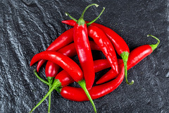 Red fresh chili pepper on a black background