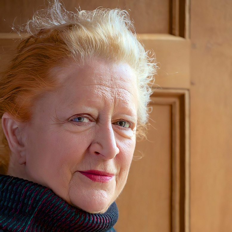 Photograph of Margaret Heffernan as she stands side on to the camera wearing a dark blue rollneck jumper in front of a wooden door.