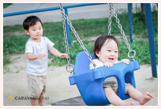 公園のブランコに乗って喜ぶ男の子