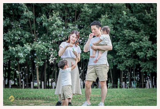 公園でしゃぼん玉を吹く親子 服装は白のTシャツでお揃いコーデ