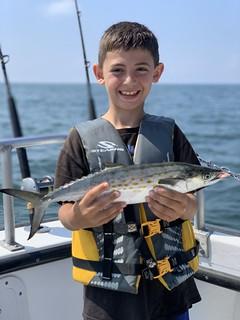 Photo of boy holding a Spanish mackerel