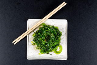 Top view, white plate with healthy seaweed salad on black background | by wuestenigel