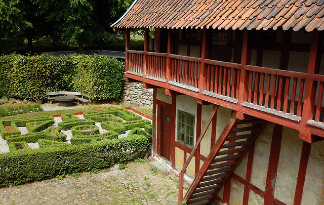 a knot garden beside an old half-timbered house in the 1864 village of the large open-air museum in Aarhus, Denmark