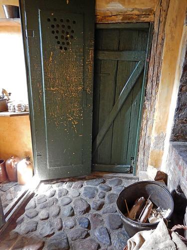 Old green door and cobblestone floor in the 1864 village of the large open-air museum in Aarhus, Denmark