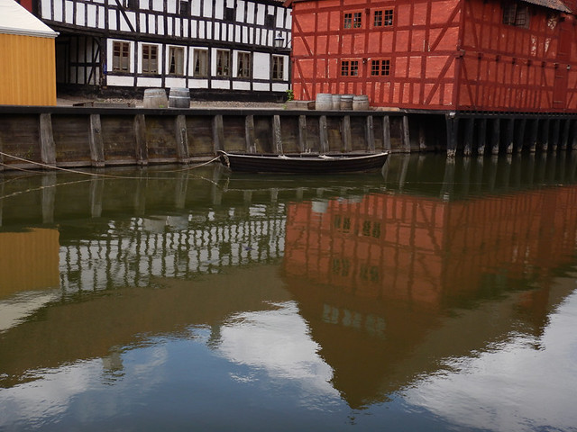 The old buildings reflected in the canal in the 1864 village of the large open-air museum in Aarhus, Denmark