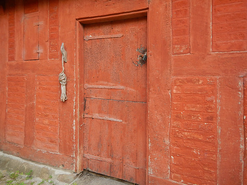 A red door in a red building in the 1864 village of the large open-air museum in Aarhus, Denmark