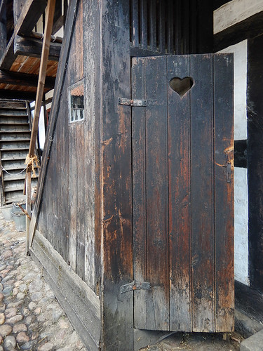 A old door with a heart carved in it in the 1864 village of the large open-air museum in Aarhus, Denmark