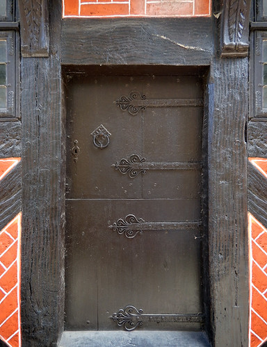 Old wooden door painted black in a half-timbered brick building in the 1864 village of the large open-air museum in Aarhus, Denmark