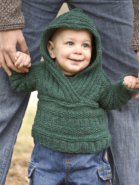 Arshile by the Berroco Design Team is a cozy baby hoodie with seed stitch and rib accents.