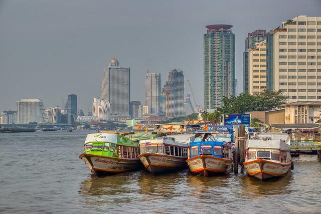 Boats on the Chao Phraya river near Asiatique with Bangkok skyline