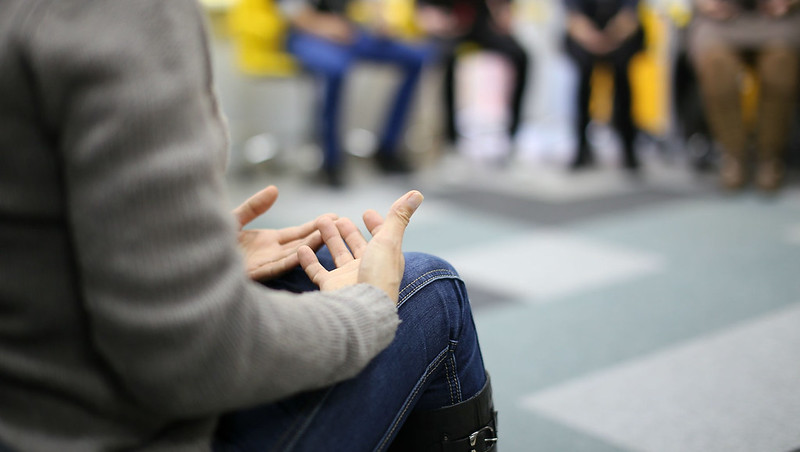 A group of people engaged in discussion with a close up on a pair of hands