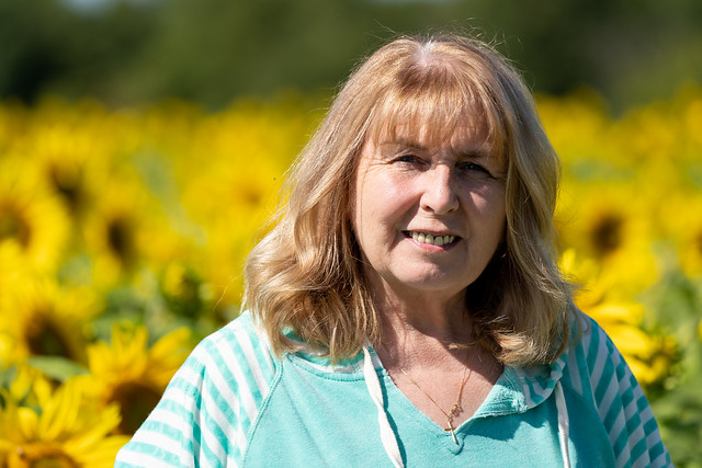 Senior woman (60-65 years) poses in front of a field of sunflowers