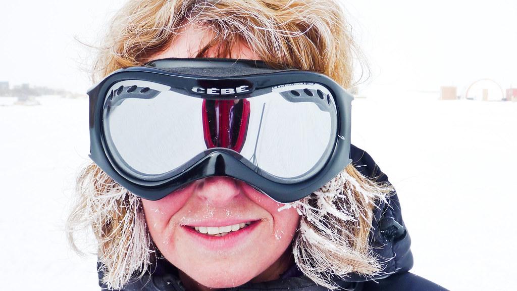 身穿防雪服的研究人员对着镜头微笑,背景是极地.