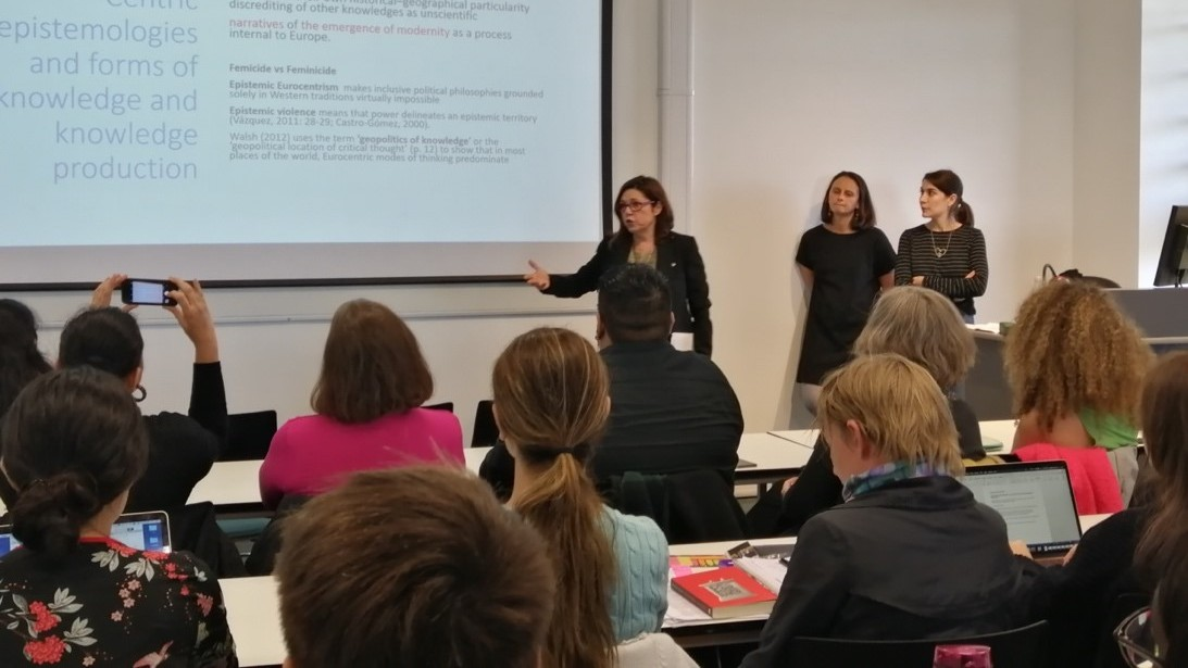 a busy lecture theatre with a woman presenting material
