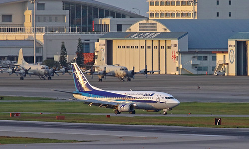 all nippon airways airline ana boeing 737500 ja305k taxi arrival naha international airport okinawa japan nickname super dolphin sunset 737 735 withdrawn service june 2020 year background pair jmsdf marine self defence force lockheed p3c orion