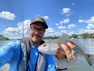 Photo of man holding a small red drum