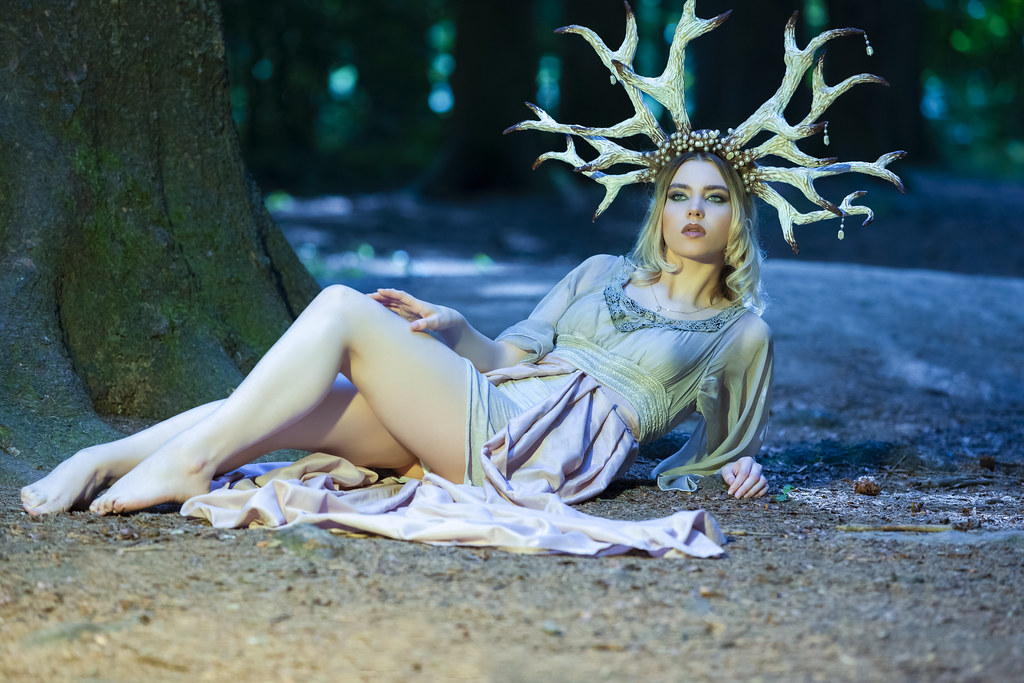 Beautiful Girl Posing With Artistic Deer Horns  In Summer Forest Near Tree on The Ground. Wearing Light Dress for Forest Nymph Concept. Art Photography.