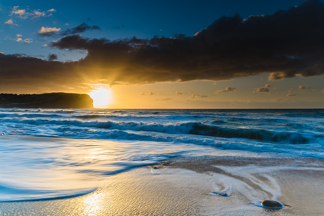 Sunrise at the beach with waves and clouds