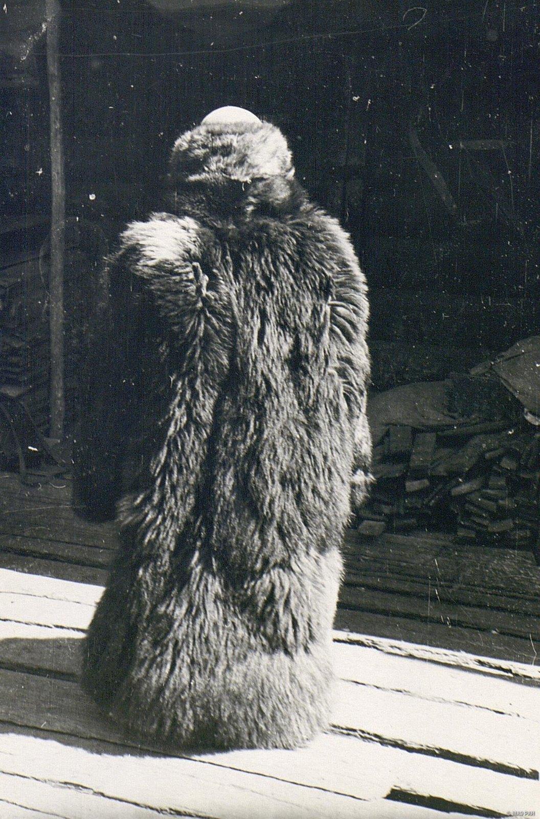 Женщина в зимней меховой одежде «дохе» (вид сзади)