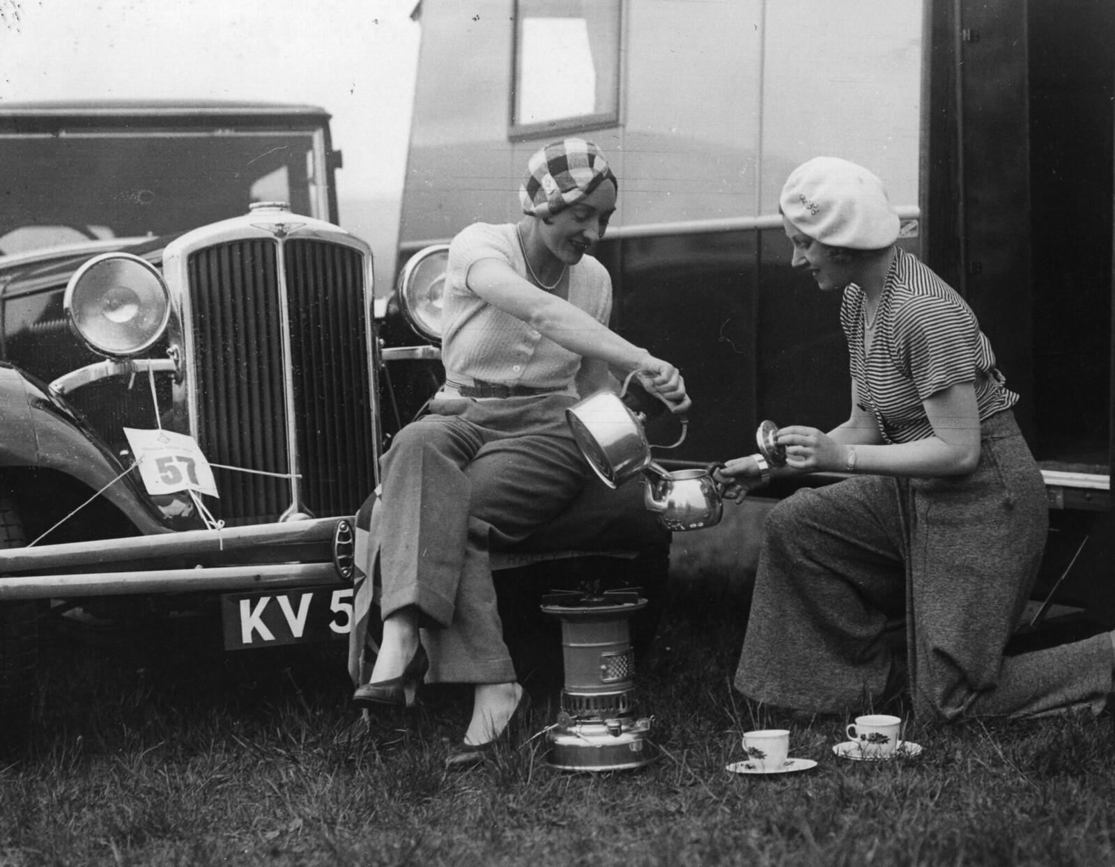 1931. Две женщины заваривают чай рядом с караваном и машиной