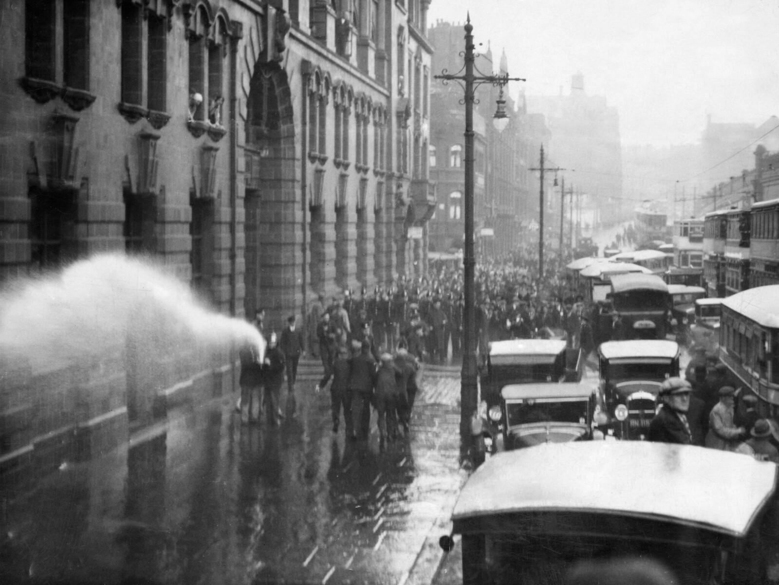 7 октября. Пожарные пытаются разогнать демонстрацию, организованную Национальным движением безработных (NUWM) на перекрестке Фэрфилд-стрит в Манчестере. Марш был протестом против сокращения пособий по безработице, инвалидности,  а так же детских пособий