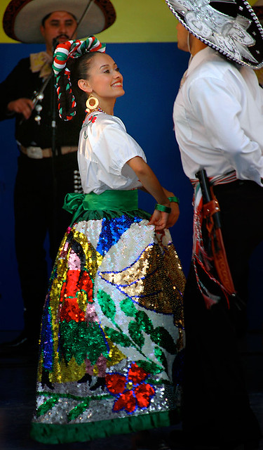 Mexican dancers wearing traditional costumes which include the China Poblano skirt covered with glittery sequins