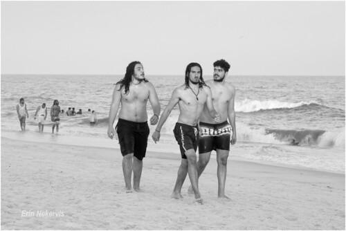 beach people wantagh newyork unitedstates men trio shorts bare expression three young frolic jonesbeach longisland summer ocean bw wave direct stare twilight sunset watersedge water