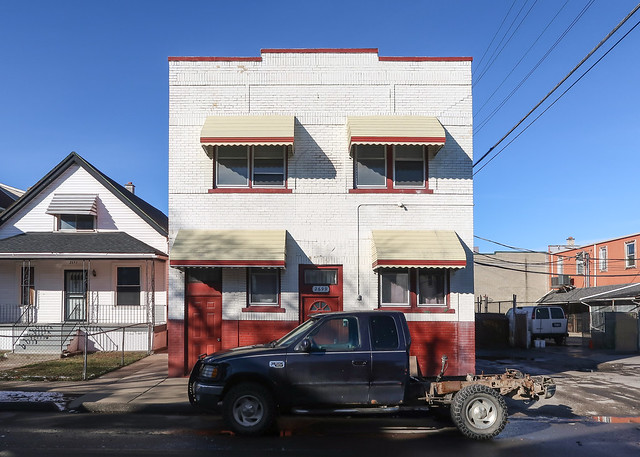Coming to us from 1925 in Hamtramck, a brick apartment building in red and white paint.