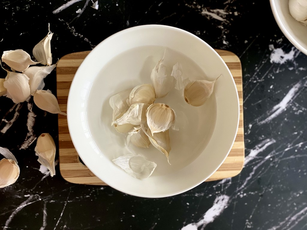 Place all garlic cloves into the hot water for approximately 1 minute. This will naturally loosen the outer layers.