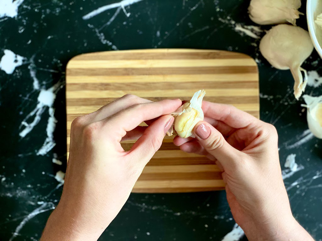 Peel of the loosened outer layer of garlic skin.
