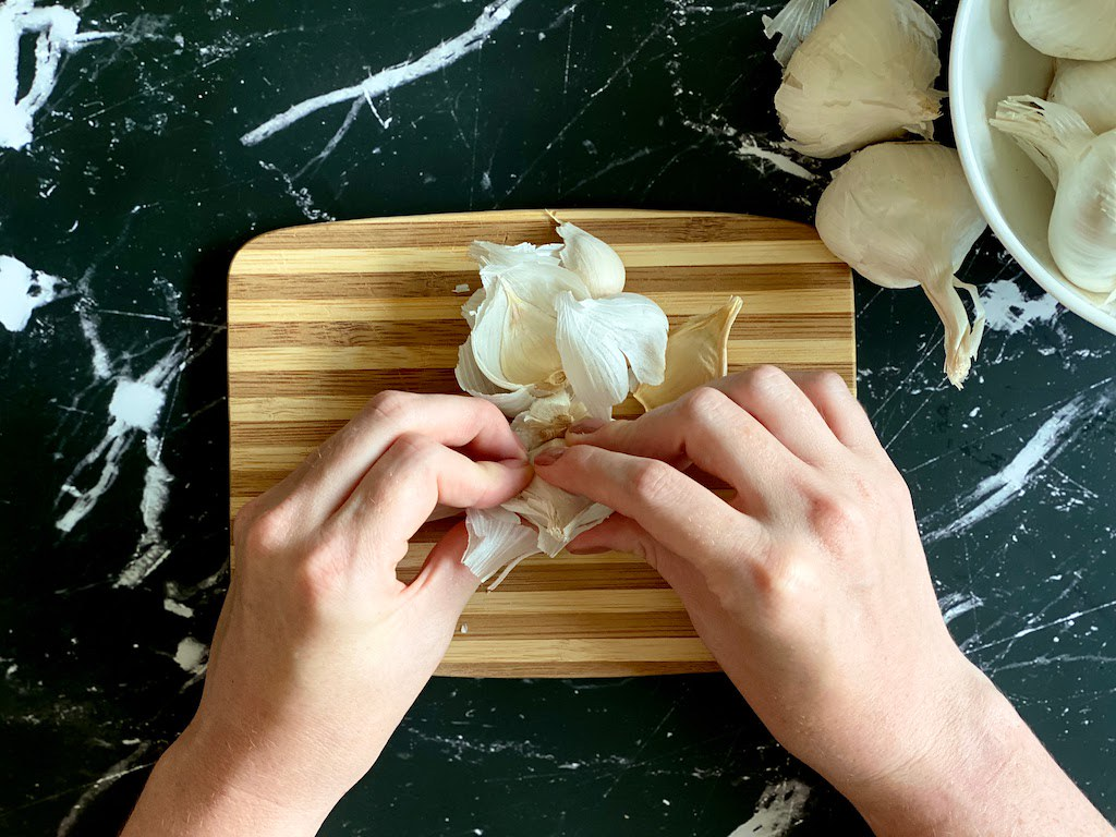 Separate however many cloves you need from the head of the garlic and place on your cutting board.