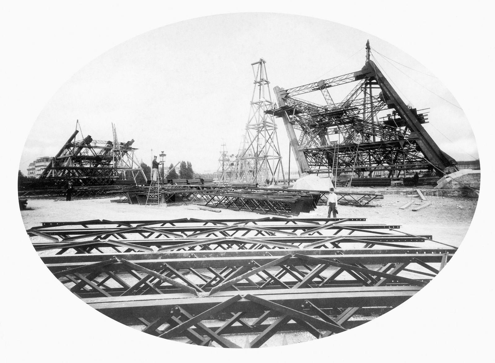 08. 1887. Строители собирают стальные балки Эйфелевой башни, одна из опор башни поддерживается деревянными лесами