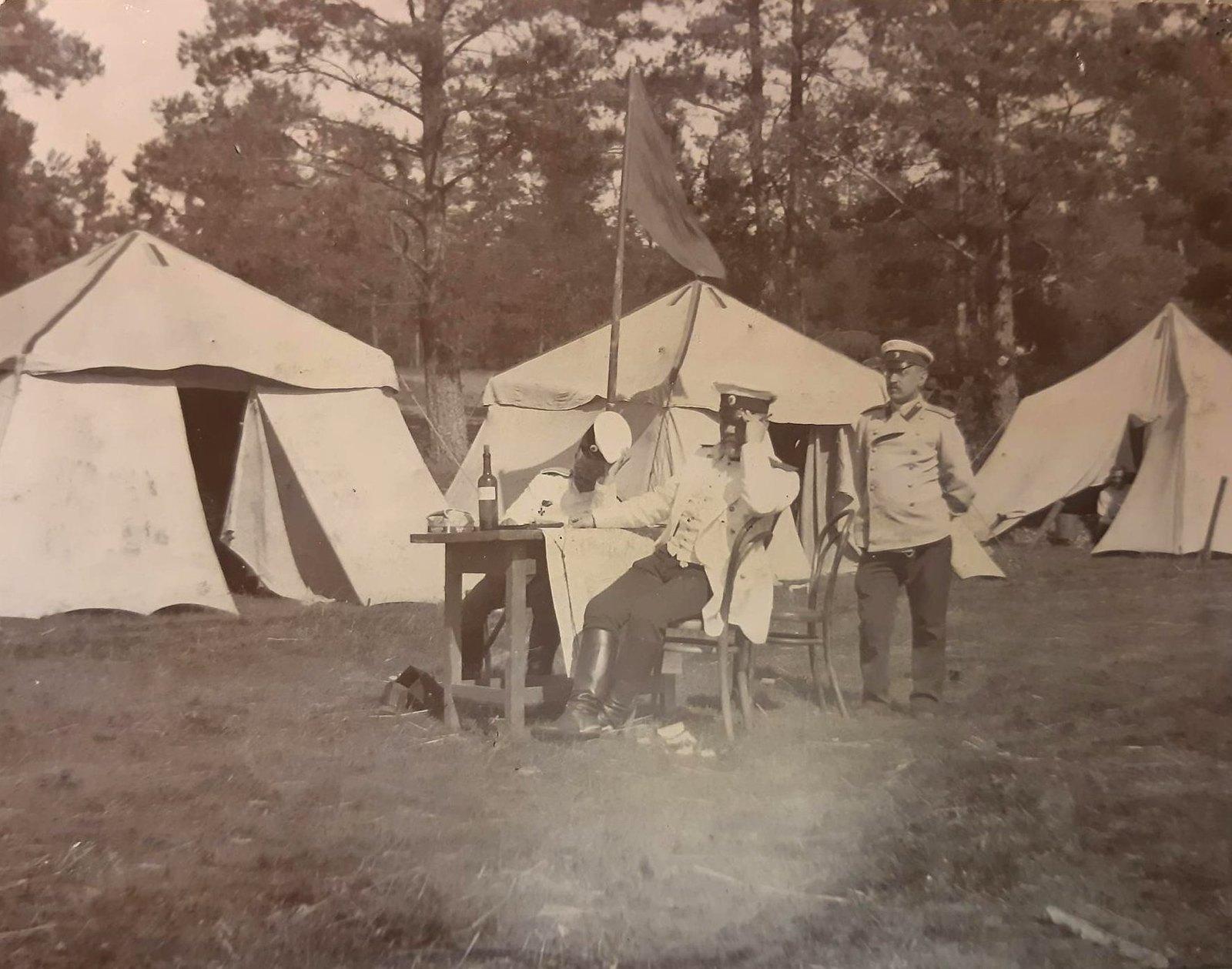 17. Офицеры за столом на фоне лагерных палаток