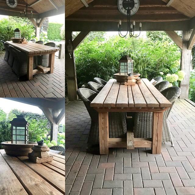 Rieten stoelen houten tuintafel onder kapschuur