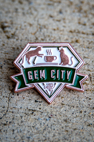 """A pin with two cats in it, and the legend """"Gem City Catfe,"""" and all done in a gem shape."""