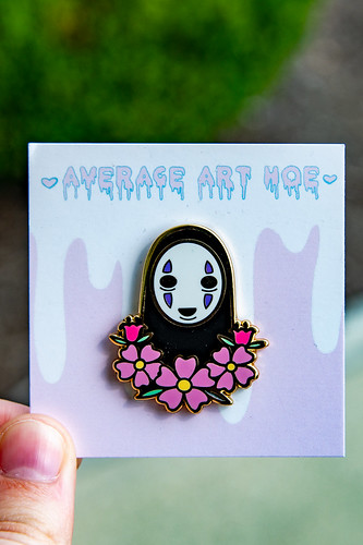 A pin of No face of Spirited Away, accompanied by pink flowers.