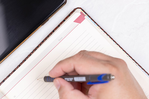 Hand with Pencil above Paper Notebook with Business concept | by wuestenigel