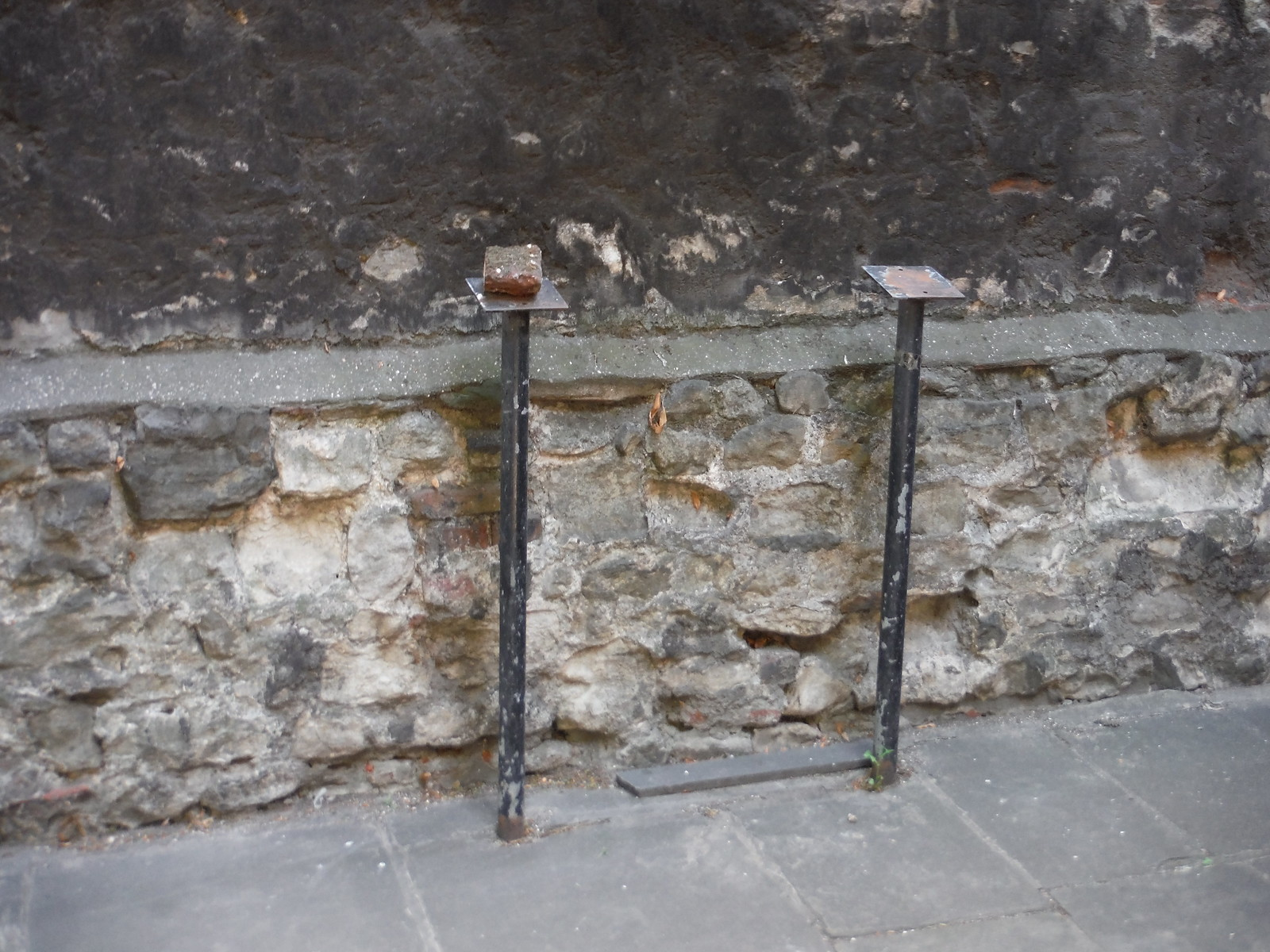 Black metal legs that held Panel 10 of the London Wall Walk, by London Wall at All-Hallows-on-the Wall Church SWC Short Walk 47 - The London Wall