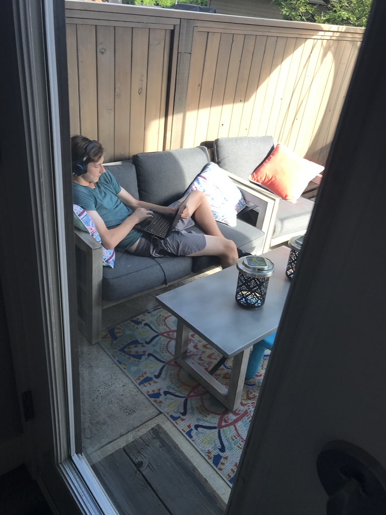 Boy working on computer outside