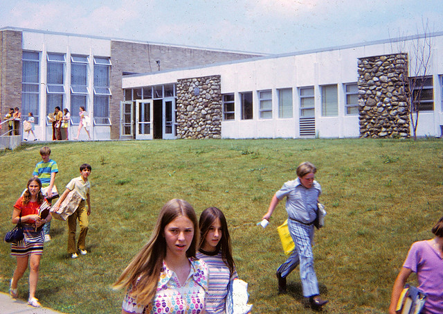 That's it, kids. School is out for the summer! Yahoo! Early teens in 1970s clothes scurry to catch the school bus back home on the last day of 7th grade. June 1971.