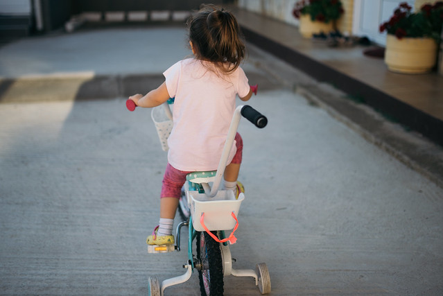 Young girl riding a bike with training wheels and push bar.