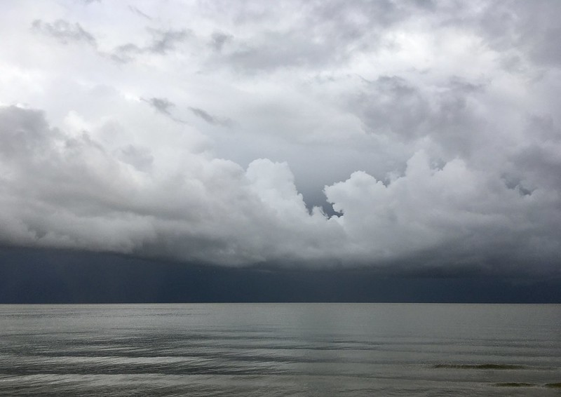 Photo of dark grey clouds over a calm and dark grey sea