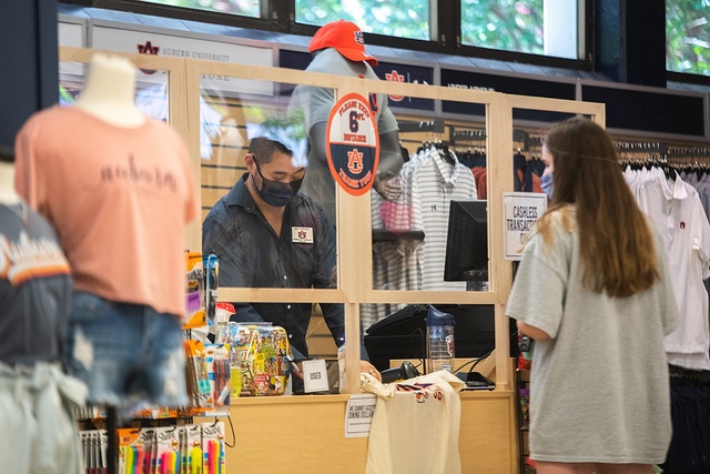 A cashier stands behind a plexiglass barrier while taking a payment from a student.
