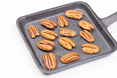 Pecan Nuts on the black steel pan above white background